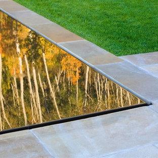 Modelo de piscina infinita, en patio, con adoquines de piedra natural