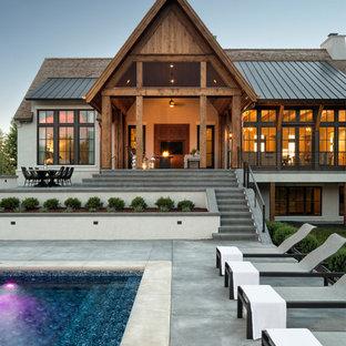Imagen de piscina campestre, rectangular, en patio trasero, con losas de hormigón