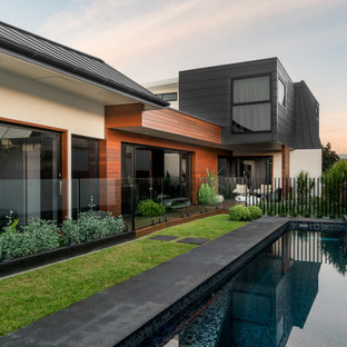 This is an example of a large contemporary backyard rectangular lap pool in Sydney with concrete slab.