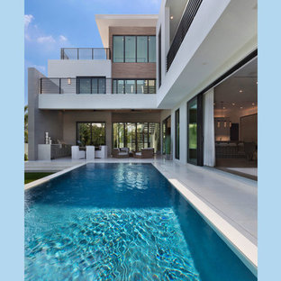 Inspiration for a mid-sized modern backyard rectangular infinity pool in Miami with stamped concrete.