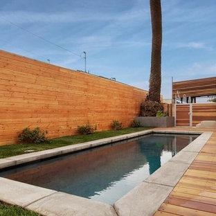 Immagine di una piscina monocorsia moderna rettangolare di medie dimensioni e dietro casa con pedane
