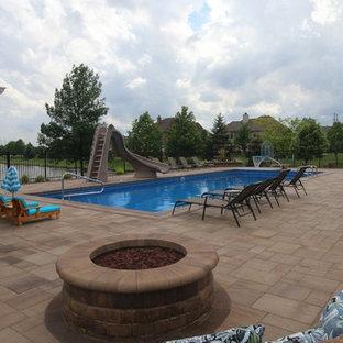 Modelo de piscina con tobogán alargada, clásica, grande, rectangular, en patio trasero, con adoquines de ladrillo