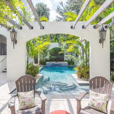 Example of an island style backyard custom-shaped pool fountain design in Orlando