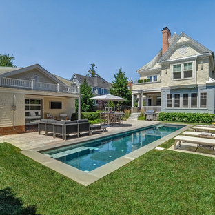 Photo of a traditional backyard rectangular lap pool in New York with a pool house and concrete pavers.