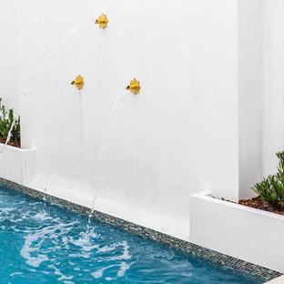Modelo de piscina con fuente natural, ecléctica, de tamaño medio, rectangular, en patio, con adoquines de piedra natural