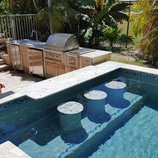 Imagen de piscinas y jacuzzis exóticos, de tamaño medio, rectangulares, en patio trasero, con adoquines de piedra natural