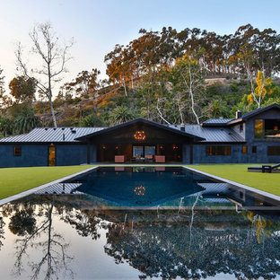 Diseño de piscina alargada, contemporánea, extra grande, rectangular, en patio trasero, con adoquines de hormigón