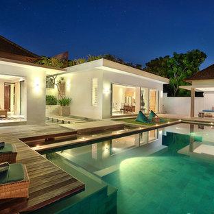 Ejemplo de casa de la piscina y piscina infinita, exótica, grande, rectangular, en patio trasero, con adoquines de piedra natural
