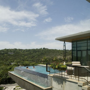 Example of a trendy rooftop rectangular infinity pool design in Austin