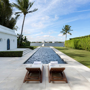 Trendy backyard concrete paver and rectangular lap pool photo in Miami
