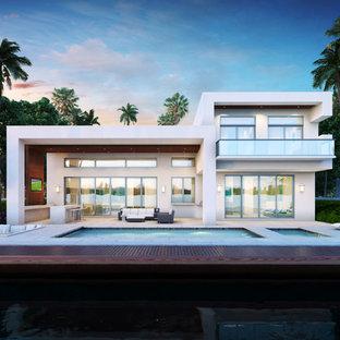 Ejemplo de piscinas y jacuzzis alargados, minimalistas, de tamaño medio, rectangulares, en patio trasero, con adoquines de hormigón