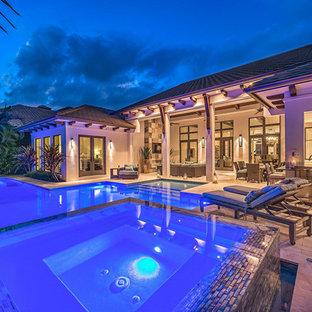 Ejemplo de piscinas y jacuzzis alargados, clásicos renovados, extra grandes, a medida, en patio trasero, con adoquines de piedra natural