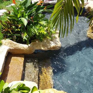 Esempio di una piccola piscina naturale tropicale personalizzata dietro casa con fontane e pavimentazioni in pietra naturale
