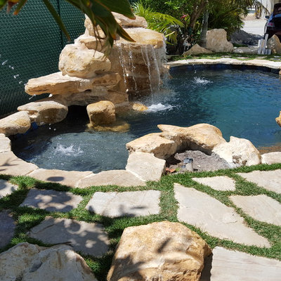 Inspiration for a small tropical backyard stone and custom-shaped natural pool fountain remodel in Miami