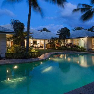 """Immagine di una piscina naturale costiera a """"C"""" di medie dimensioni e dietro casa con pavimentazioni in mattoni"""