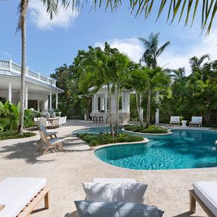 Foto de piscina natural, marinera, de tamaño medio, tipo riñón, en patio trasero, con suelo de hormigón estampado