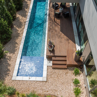 Modelo de piscina alargada, actual, de tamaño medio, rectangular, en patio trasero, con entablado