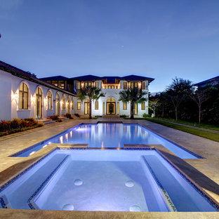 Modelo de piscinas y jacuzzis mediterráneos, grandes, rectangulares, en patio trasero, con adoquines de hormigón