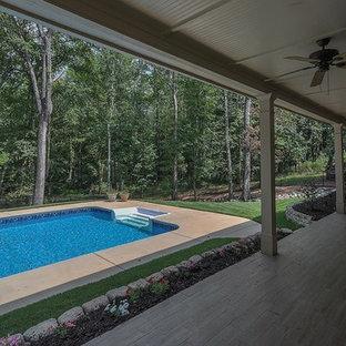 Foto de piscina natural, de estilo americano, grande, rectangular, en patio trasero, con adoquines de hormigón