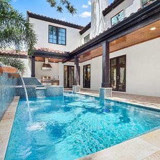 Mediterranes Sportbecken hinter dem Haus in rechteckiger Form mit Wasserspiel in Tampa