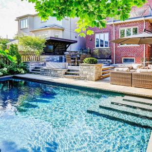 Modelo de piscina tradicional renovada, de tamaño medio, rectangular, en patio trasero, con adoquines de piedra natural