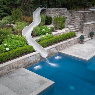 Imagen de piscina con tobogán alargada, actual, grande, rectangular, con adoquines de piedra natural