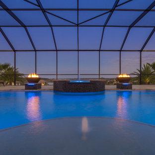 Idee per un'ampia piscina coperta mediterranea personalizzata con una vasca idromassaggio e pavimentazioni in pietra naturale