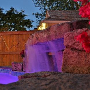 Imagen de piscina con fuente alargada, tradicional renovada, de tamaño medio, a medida, en patio trasero, con losas de hormigón