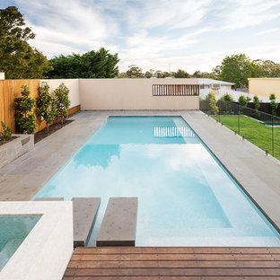 Foto di un'ampia piscina minimalista rettangolare dietro casa con pavimentazioni in pietra naturale