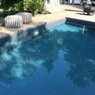 Foto de piscinas y jacuzzis naturales, rústicos, grandes, en forma de L, en patio trasero, con entablado
