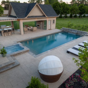 This is an example of a mid-sized contemporary backyard rectangular lap pool in Toronto with a pool house and stamped concrete.