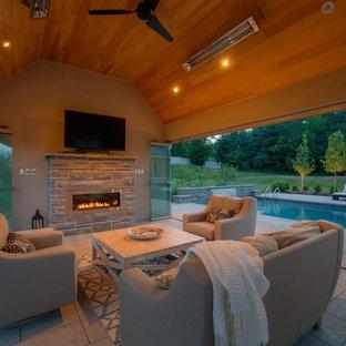 Foto de casa de la piscina y piscina alargada, contemporánea, de tamaño medio, rectangular, en patio trasero, con suelo de hormigón estampado