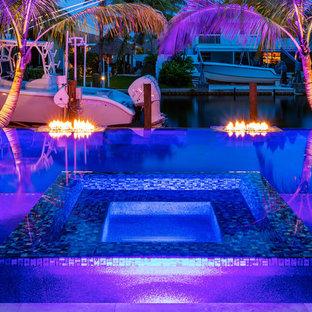 Exemple d'une piscine à débordement et arrière exotique de taille moyenne et sur mesure avec un bain bouillonnant et des pavés en pierre naturelle.