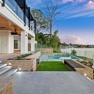 Imagen de piscina natural, minimalista, pequeña, rectangular, en patio trasero, con privacidad y suelo de baldosas