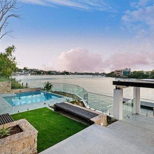 Foto de piscina natural, minimalista, pequeña, rectangular, en patio trasero, con privacidad y suelo de baldosas