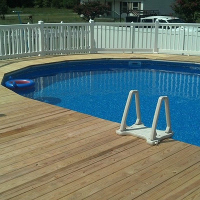 Pool - mid-sized traditional backyard round aboveground pool idea in Other with decking