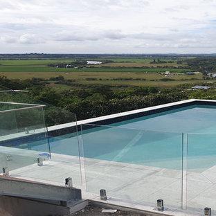 Diseño de piscina elevada, actual, de tamaño medio, rectangular, en patio delantero, con entablado