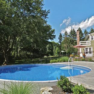 Foto de piscina elevada, tradicional, grande, redondeada, en patio trasero, con suelo de hormigón estampado
