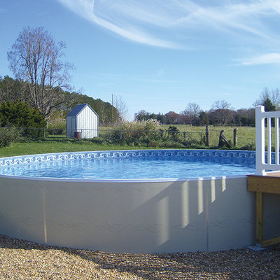 Example of a mid-sized classic backyard round aboveground pool design in Other
