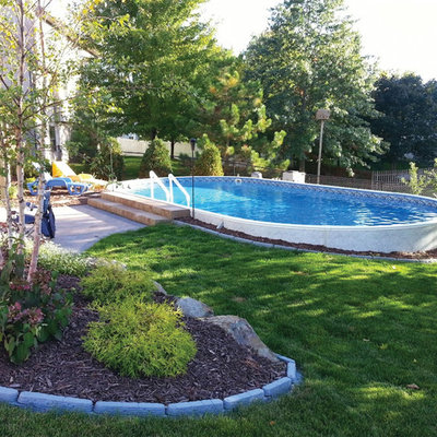 Example of a mid-sized trendy backyard concrete and round aboveground pool design in Cleveland