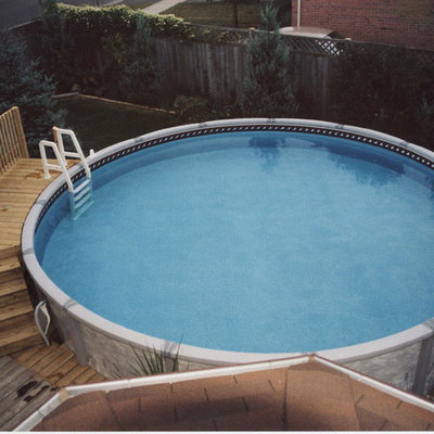 Pool - mid-sized traditional backyard round aboveground pool idea in Toronto with decking