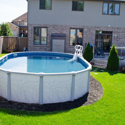 Inspiration for a mid-sized timeless backyard round aboveground pool remodel in Toronto