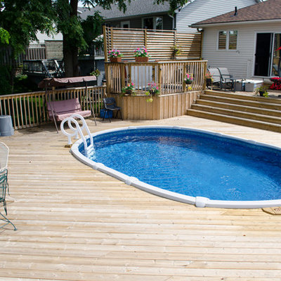 Example of a mid-sized classic backyard round aboveground pool design in Toronto