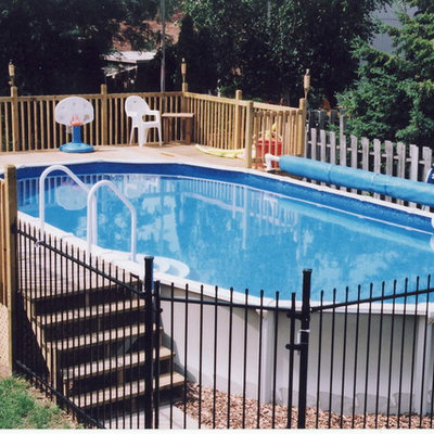 Inspiration for a mid-sized timeless backyard round aboveground pool remodel in Toronto with decking