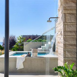 Réalisation d'une très grand piscine avant et hors-sol design rectangle avec une dalle de béton et un bain bouillonnant.
