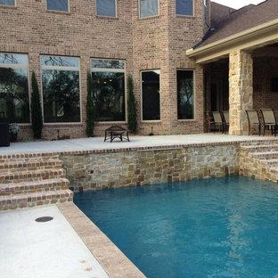 Imagen de piscina con fuente alargada, de estilo americano, de tamaño medio, rectangular, en patio trasero, con adoquines de ladrillo