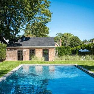 Modelo de piscina alargada, romántica, de tamaño medio, rectangular, en patio trasero, con adoquines de hormigón