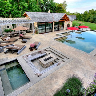 Design ideas for a large mediterranean front yard rectangular pool in Toronto with a hot tub and stamped concrete.