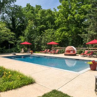 Foto de piscinas y jacuzzis alargados, tradicionales, grandes, rectangulares, en patio lateral, con suelo de hormigón estampado