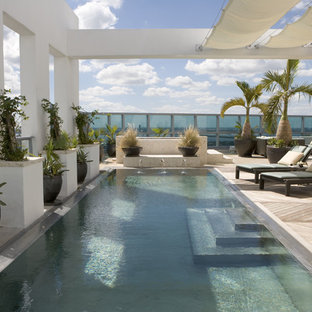 Design ideas for a large tropical backyard rectangular pool in Philadelphia with a water feature and decking.